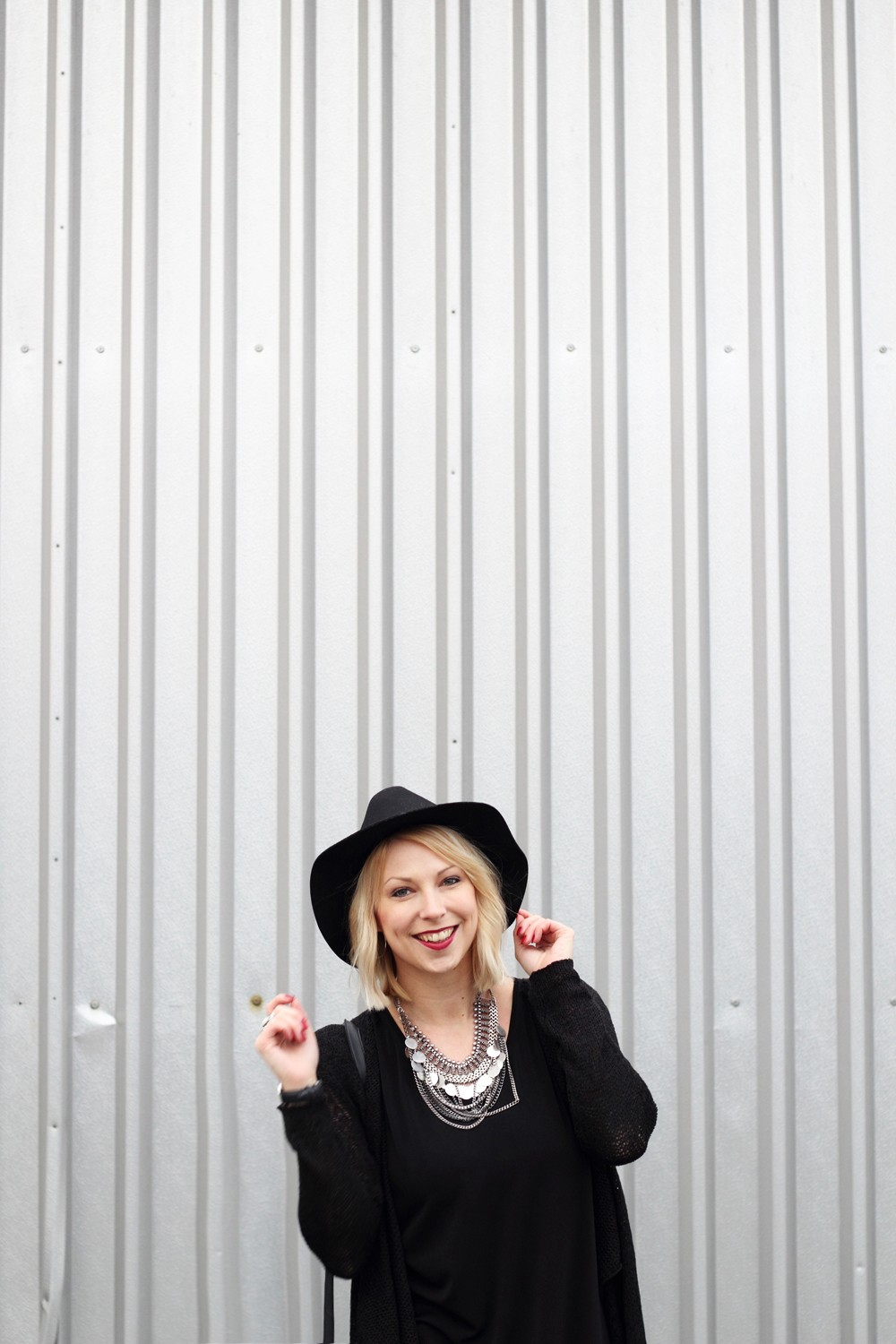 Fashionblogger Karlsruhe Outfit all in black Flared Jeans Cardigan Hut Fransentasche Kleid 12