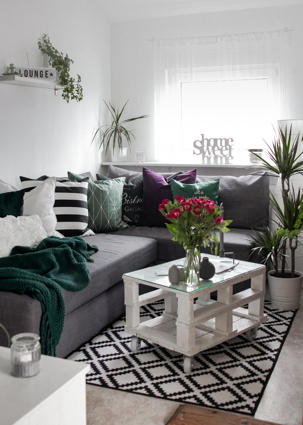Wohnzimmer Einrichtung lila gruen Deko Kissen Vasen Couchtisch aus